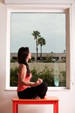 Attraktive Frau, die Yoga durch Fenster tut Lizenzfreie Stockfotografie