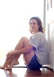 Attraktive Frau, die zu Hause auf Bretterboden sitzt stockbild
