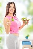 Attraktive Frau, die zu Hause einen Salat hält Stockfoto