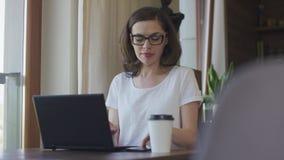 Attraktive Frau, die zu Hause Smartphone und Laptop verwendet stock video
