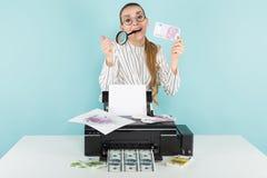 Attraktive Frau druckt Bargeld mit Lupe Stockbild