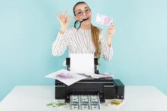 Attraktive Frau druckt Bargeld mit Lupe Stockfotografie