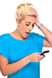 Attraktive Frau entsetzt durch Handy-Meldung Stockbild