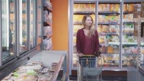 Attraktive Frau geht in Supermarkt und in überzeugtes wählendes gesundes Produkt stock video footage