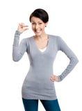 Attraktive Frau gestikuliert kleine Menge Stockfoto