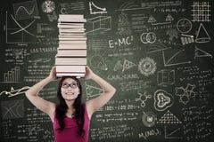 Attraktive Frau holen Bücher auf ihrem Kopf an der Klasse Stockfoto