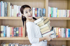 Attraktive Frau holen Stapel Bücher in der Bibliothek Lizenzfreies Stockbild