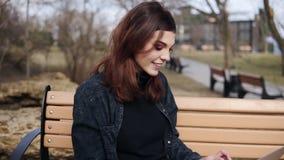 Attraktive Frau in ihren 20 ` Si, die auf der Bank am Park etwas auf ihrer Laptoptastatur schreibend sitzen Genießen von Freizeit stock video