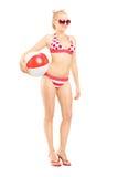 Attraktive Frau im Bikini, der einen Ball hält Stockfoto