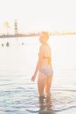 Attraktive Frau im Bikini am Ufer nahe Leuchtturm Stockfotografie