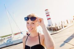 Attraktive Frau im Bikini am Ufer nahe Leuchtturm Stockbild
