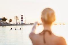 Attraktive Frau im Bikini am Ufer nahe Leuchtturm Lizenzfreies Stockfoto