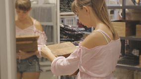 Attraktive Frau im Haushaltsgeschäft Junge kaukasische weibliche öffnende Holzkiste mit Überraschung vor dem Spiegel stock video