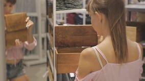Attraktive Frau im Haushaltsgeschäft Junge kaukasische weibliche öffnende Holzkiste vor dem Spiegel stock footage