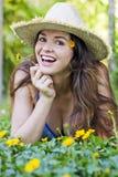 Attraktive Frau im Hut und in den Blumen Stockfotos