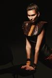 Attraktive Frau im Leder auf Stuhl Stockbilder