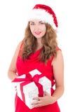 Attraktive Frau im rotem Kleid und in Sankt-Hut mit dem Weihnachten prese Stockfotografie