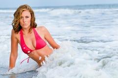 Attraktive Frau im roten Bikini spritzte durch Welle Lizenzfreies Stockfoto