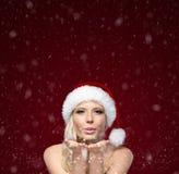 Attraktive Frau im Weihnachtsschutzkappen-Schlagkuß Stockfotografie