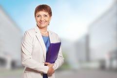 Attraktive Frau 50 Jahre alt mit einem Ordner Stockfoto