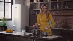 Attraktive Frau kocht das Mittagessen mit Lächeln im Haus stock video