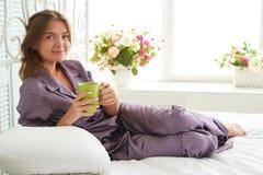 Attraktive Frau am Kopfende mit einer Tasse Tee im Schlafzimmeresprit lizenzfreie stockfotos