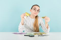 Attraktive Frau mit Bargeld und Lupe Lizenzfreie Stockfotografie
