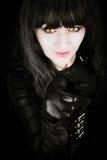 Attraktive Frau mit dem Katzenaugentragen schwarz und dem Zeigen Stockbild