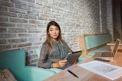 Attraktive Frau mit dem schönen Lächeln, das mit tragbarem Netzbuch in der Kaffeestube sitzt Lizenzfreie Stockfotografie