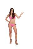 Attraktive Frau mit der rosa Badebekleidung, die etwas anzeigt Stockfotos