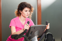 Attraktive Frau mit der Sportkleidung, die das Innenradfahren tut Stockfotos