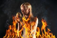 Attraktive Frau mit einem Dracheei im Feuer Stockfotos
