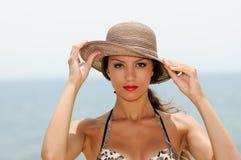 Attraktive Frau mit einem Sonnenhut auf einem tropischen Strand Lizenzfreie Stockfotografie