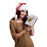 Attraktive Frau mit einem Weihnachtshut und einem Geschenk Stockfoto