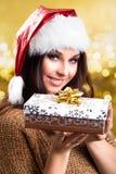 Attraktive Frau mit einem Weihnachtshut und einem Geschenk Lizenzfreie Stockbilder
