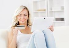 Attraktive Frau mit einer Kreditkarte und einer Tablette Lizenzfreies Stockfoto
