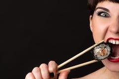 Attraktive Frau mit emotionalem Gesicht Rolle essend stockbild