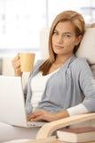Attraktive Frau mit Kaffee und Laptop Lizenzfreies Stockfoto