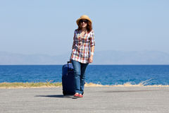 Attraktive Frau mit Koffer auf dem Strand Stockfotos