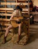 Attraktive Frau mit Landblick, schoss zuhause, amerikanischer Landhausstil Blondes Mädchen mit schwarzem Cowboyhut und Gitarre Lizenzfreie Stockfotos