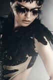 Attraktive Frau mit schwarzen Federn auf Schultern Stockbild