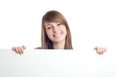 Attraktive Frau mit unbelegtem Zeichen. Lächeln. stockbild
