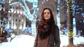 Attraktive Frau nachts schneebedeckte Heilige Nacht lächelt, die Kamera vor verzierten funkelnden Lichtern des Parks betrachtend  Stockbild