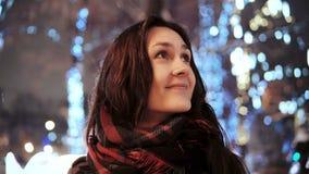 Attraktive Frau nachts schneebedeckte Heilige Nacht lächelt, die Kamera vor verzierten funkelnden Lichtern des Parks betrachtend  Stockfoto