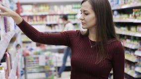 Attraktive Frau nimmt Duschgel und schnüffelt es im Supermarkt, Gefühl wie und Abneigung stock video