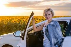 Attraktive Frau parkte nahe einem Feld von Sonnenblumen Stockbild