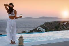 Attraktive Frau am Pool genießt den Sonnenuntergang über dem Mittelmeer lizenzfreies stockfoto