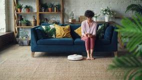 Attraktive Frau schaltet auf Sofa sitzenden und stillstehenden den Roboterstaubsauger dann unter Verwendung des Smartphone ein, w stock footage