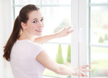 Attraktive Frau schließt Fenster Stockfotografie