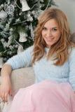 Attraktive Frau sitzen nahe Weihnachtsbaum Stockfotografie
